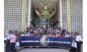 Large group of people with a banner outside of a building. (Photo Credit: State Department)